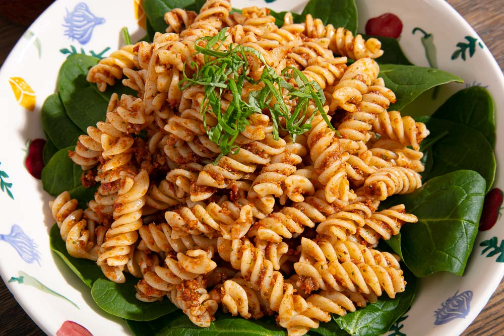 Chiffonade basil on top of red pesto pasta.