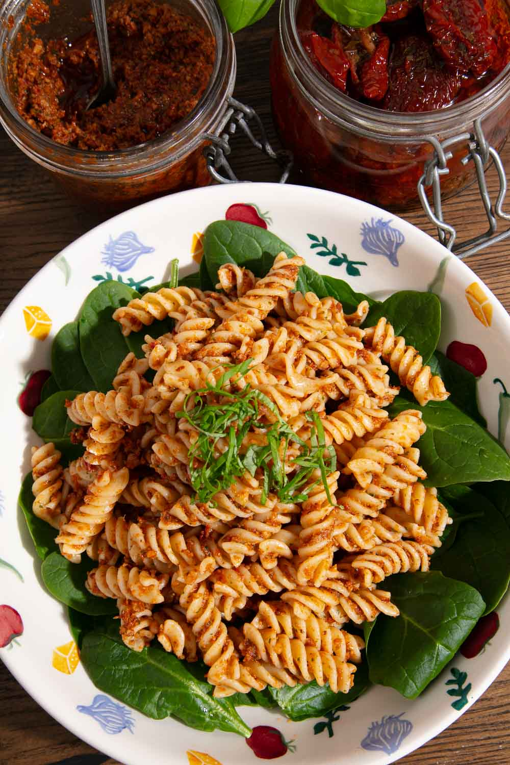 Red pesto pasta on a bed of fresh spinach leaves, a jar of homemade red pesto and a jar of sundried tomatoes in the background.