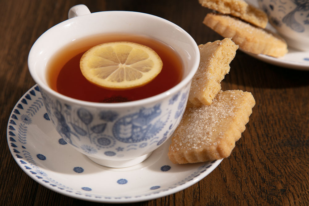 A cup of Earl Grey tea with a snapped shortbread biscuit on the saucer.