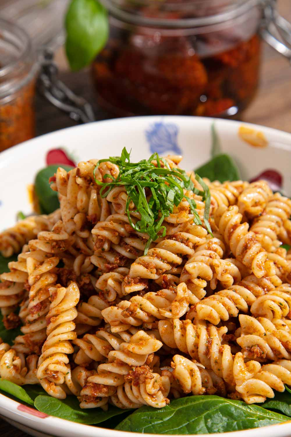 A bowl of red pesto pasta topped with shredded basil.
