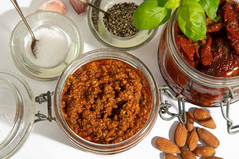 A jar of sundried tomato pesto surrounded by the ingredients to make it.