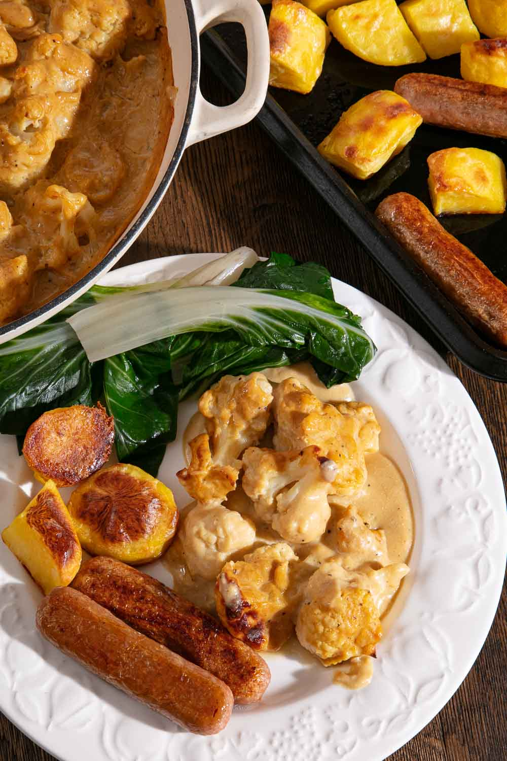 Vegan cauliflower cheese, roast potatoes, vegan sausages and chard on a plate with serving dishes in the background.