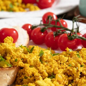 Scrambled Tofu on sourdough toast with cherry tomatoes on the vine.