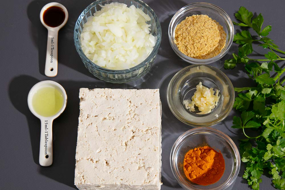 Ingredients for scrambled tofu, laid out on a chopping board.