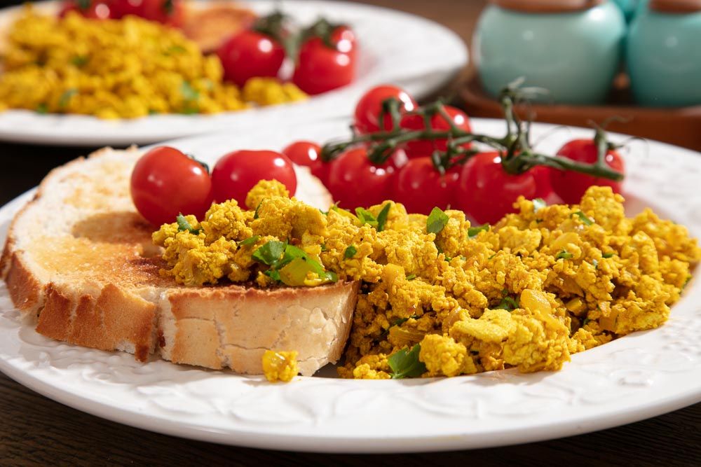 Tofu scramble on toast with cherry tomatoes.
