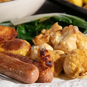 Vegan cauliflower cheese served with sausages, roast potatoes and swiss chard.