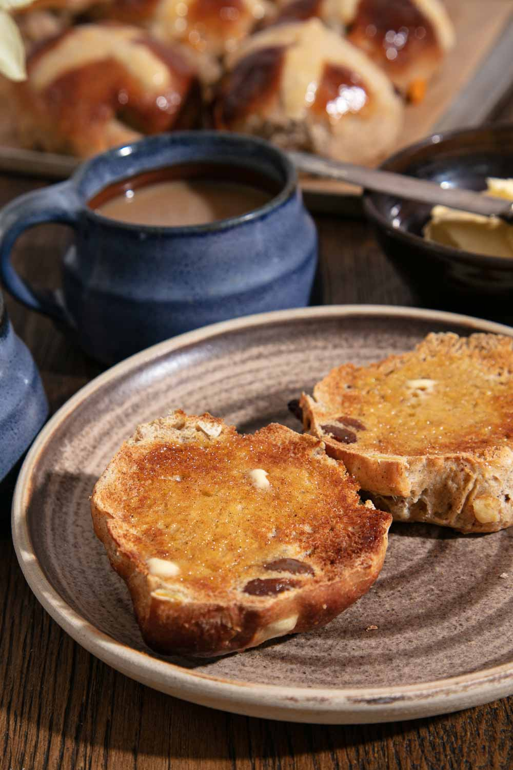 Toasted vegan hot cross bun spread with butter. Served with a cup of tea.