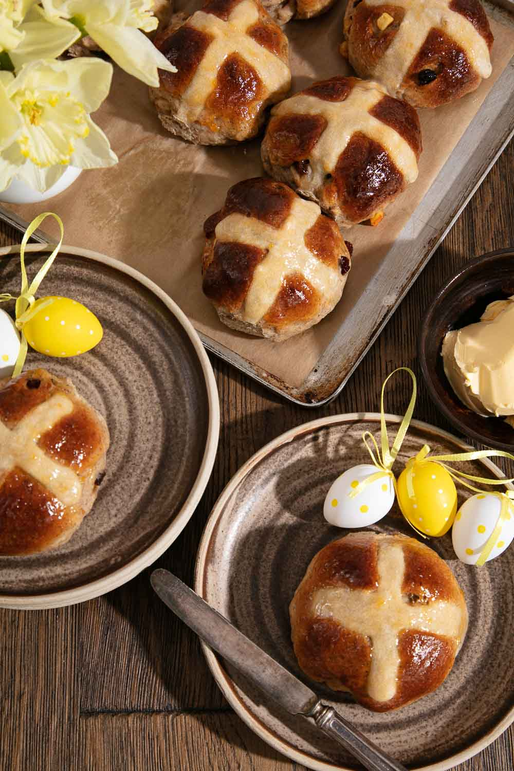 Homebaked Vegan Hot Cross Buns on a baking tray. Two buns on plates with Easter egg decorations.
