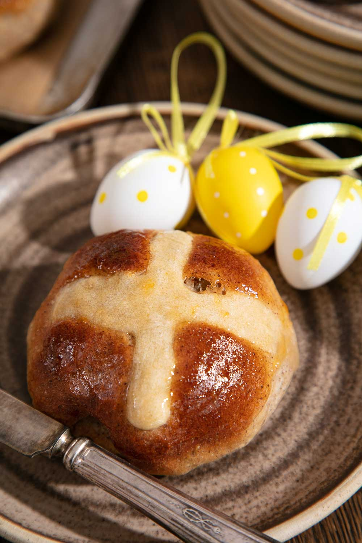 Vegan Hot Cross Bun with decorative eggs on a rustic plate.