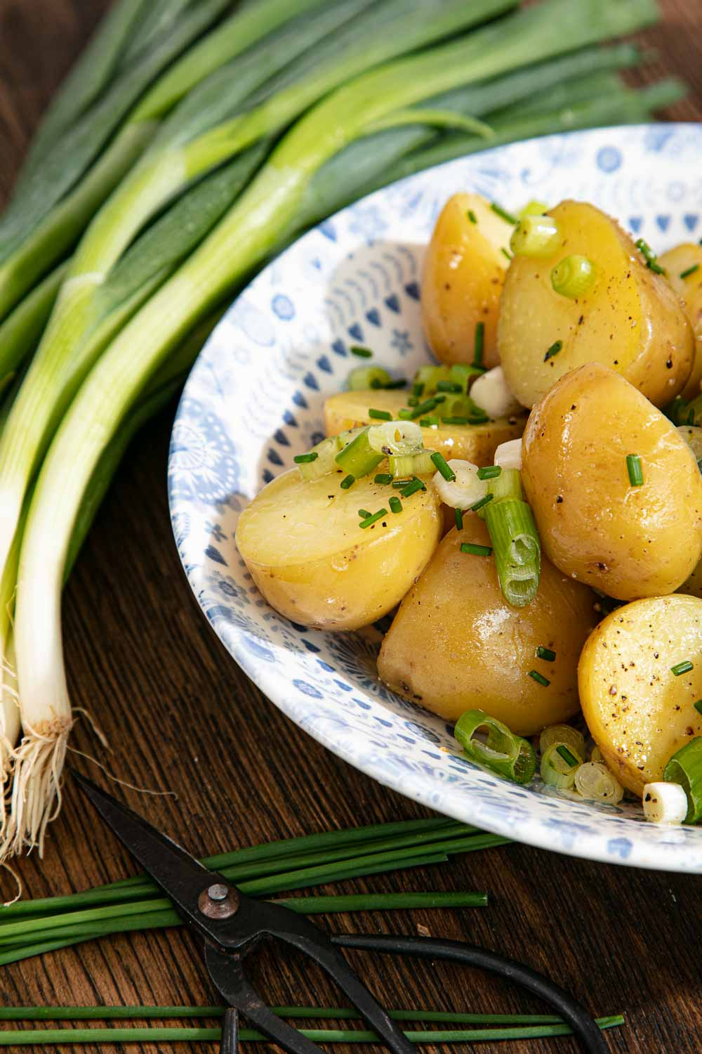 No Mayo Potato Salad in a blue and white patterned bowl with a bunch of chives to its side.