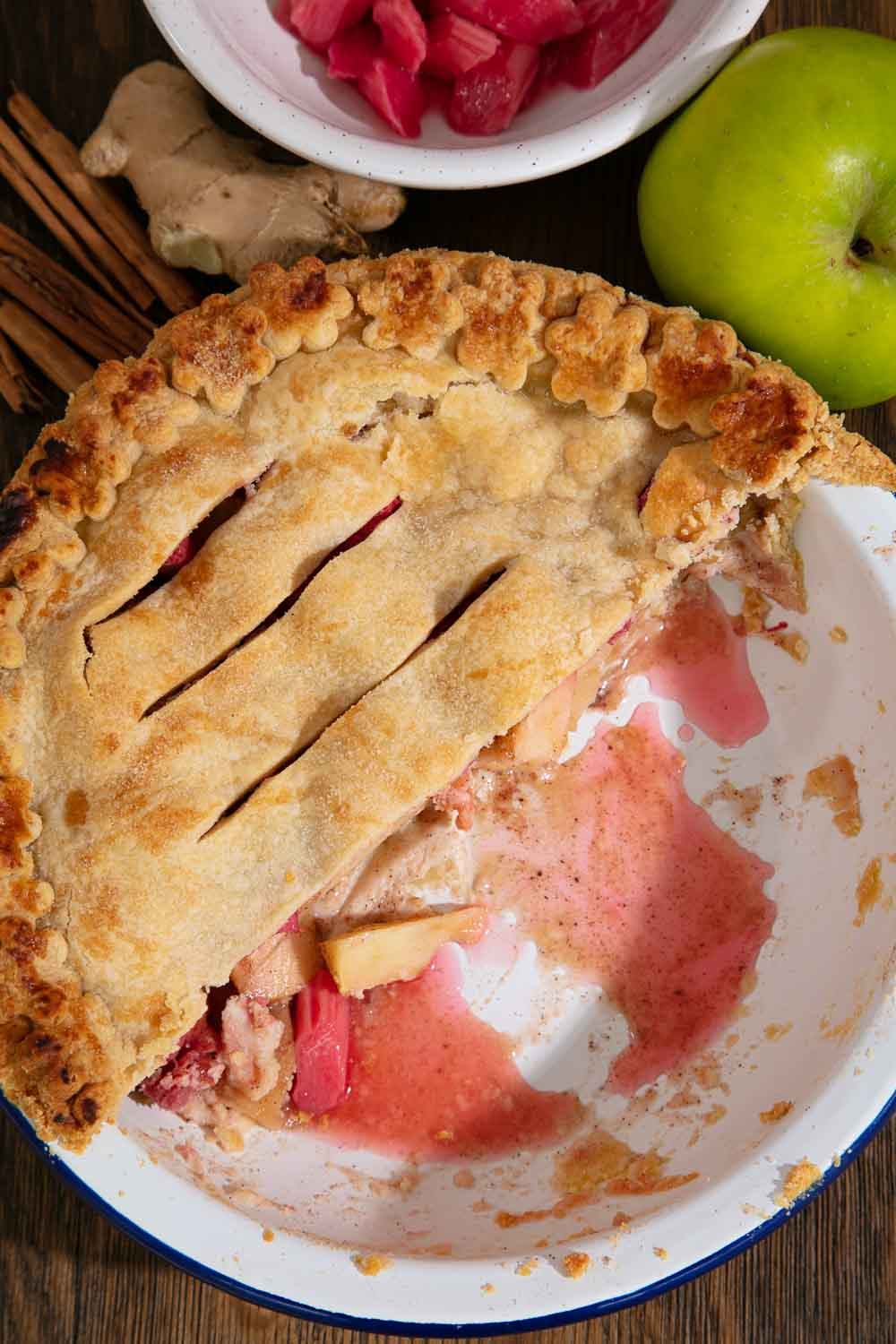 Rhubarb and apple pie surrounded with the ingredients to make it.
