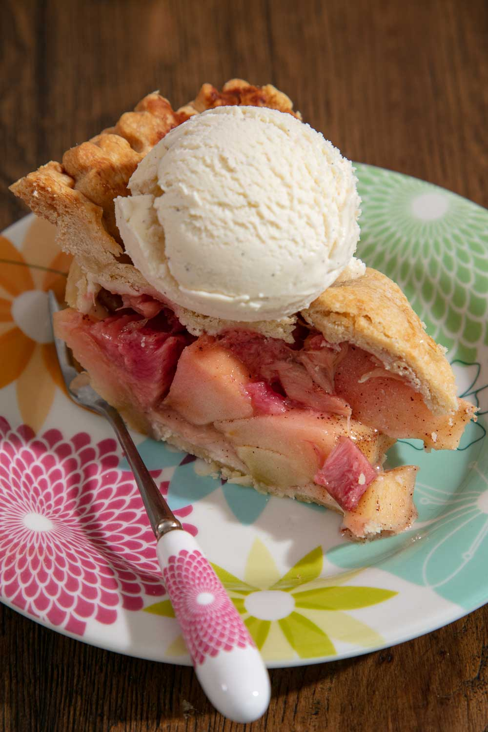 A slice of apple and rhubarb pie with a scoop of vanilla ice cream.