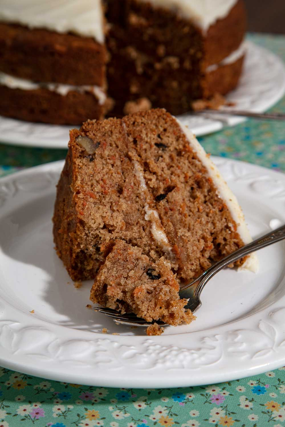 A slice of vegan carrot cake with a forkful ready to eat.