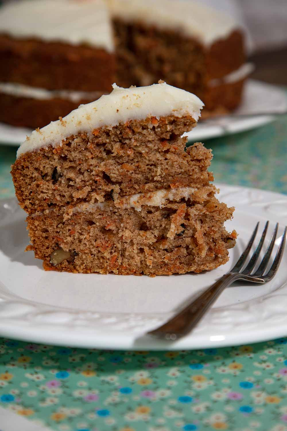 A slice of vegan carrot cake on a white plate with a silver cake fork.