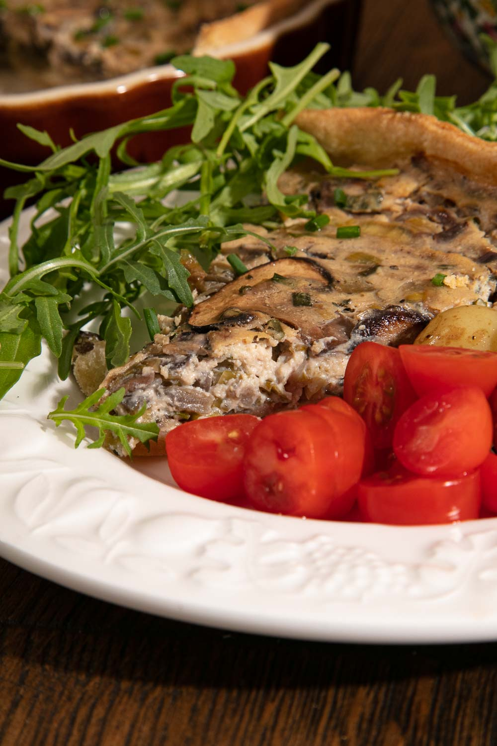 A slice of vegan quiche showing the creamy mushroom filling. Plated with tomatoes and rocket.