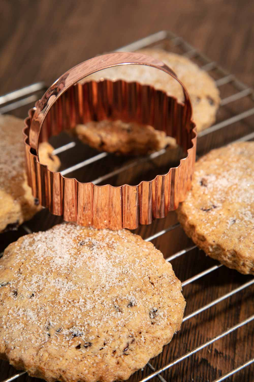 Easter Biscuits cooling on a wire rack, topped with a copper biscuit cutter.