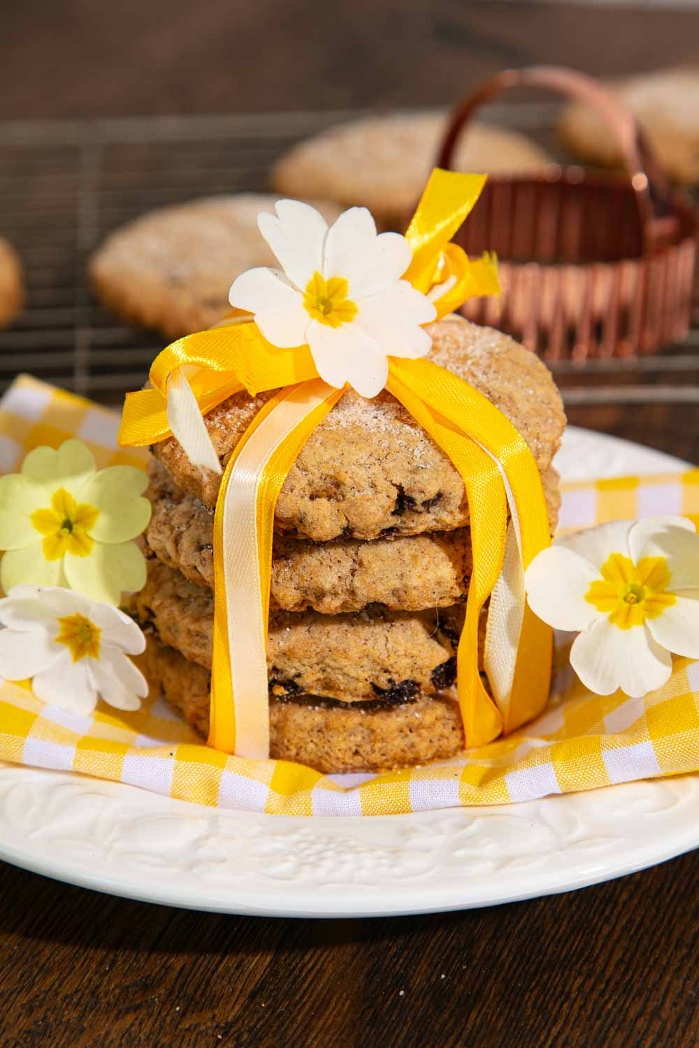 A stack of vegan Easter biscuits tied with yellow ribbons and topped with fresh primrose flowers.