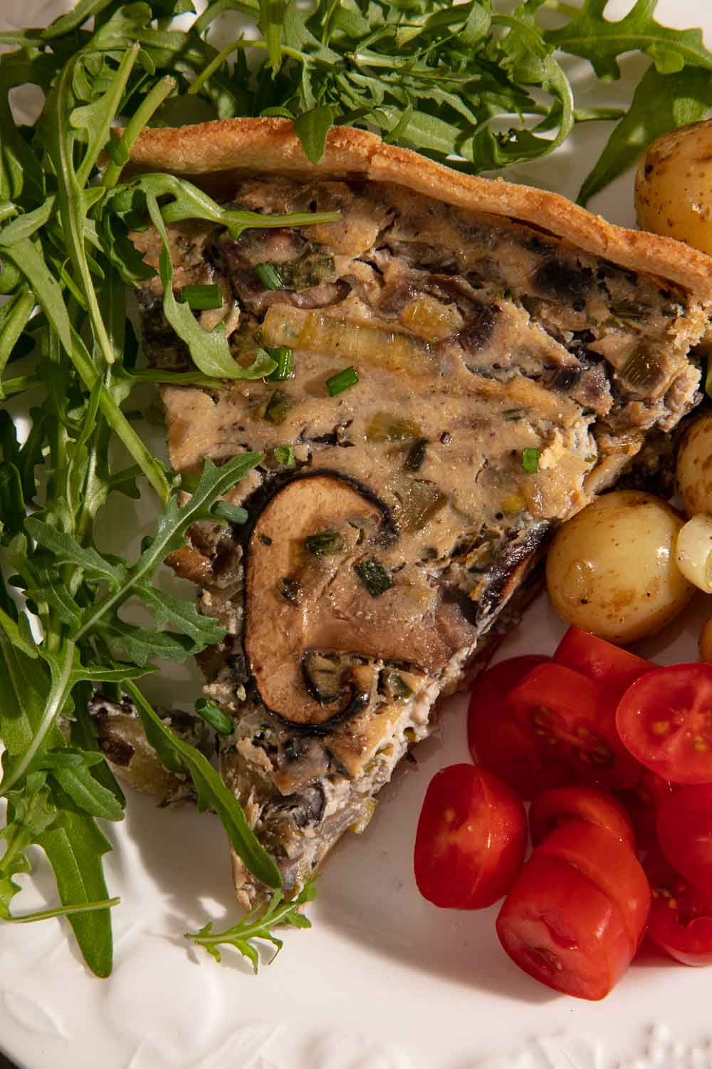 A slice of vegan mushroom quiche with new potato salad, sliced tomatoes and rocket.