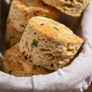 Vegan savoury scones piled into a cloth lined basket.