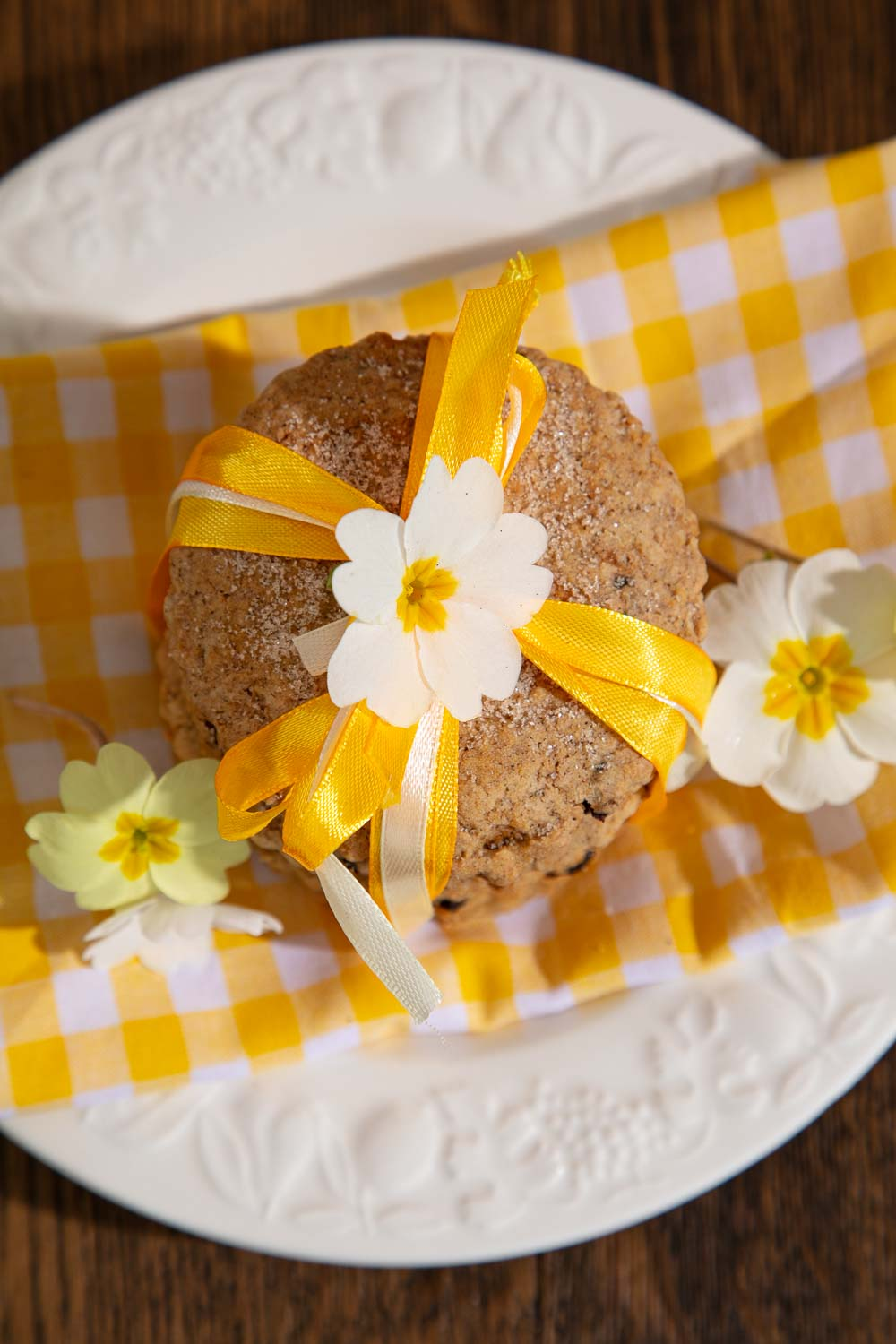 A stack of Vegan Easter Biscuits tied with yellow ribbons, decorated with fresh primrose flowers. Sitting on yellow gingham.