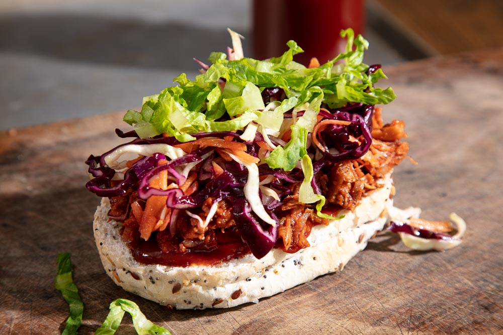 BBQ Jackfruit topped with red cabbage coleslaw and green lettuce leaves.