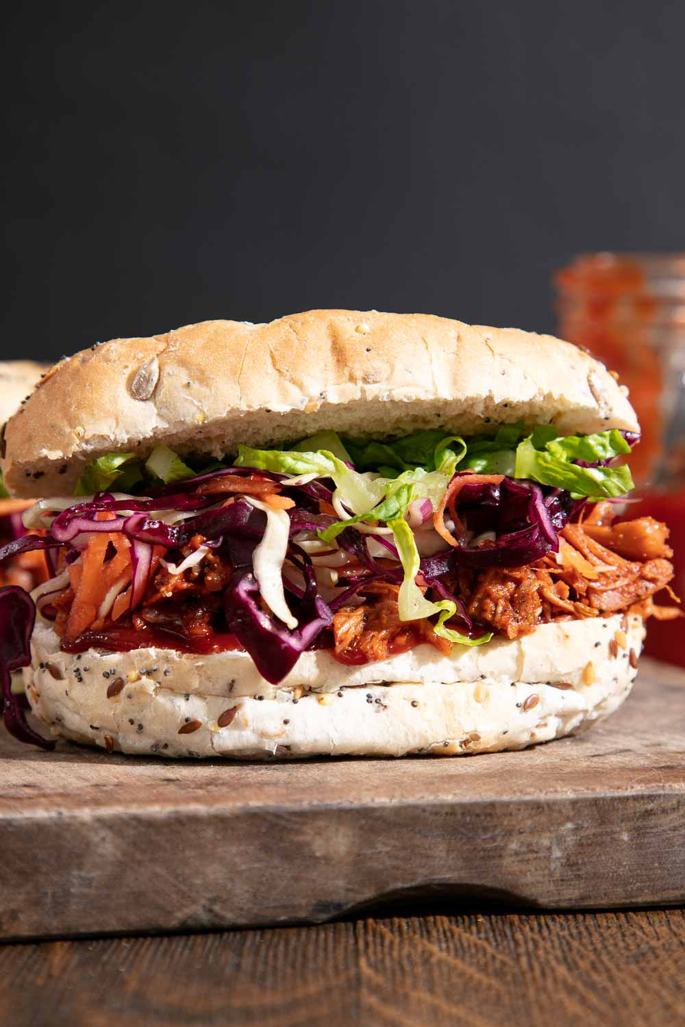 Barbecued jackfruit in a seeded bun with red cabbage coleslaw and green lettuce leaves.