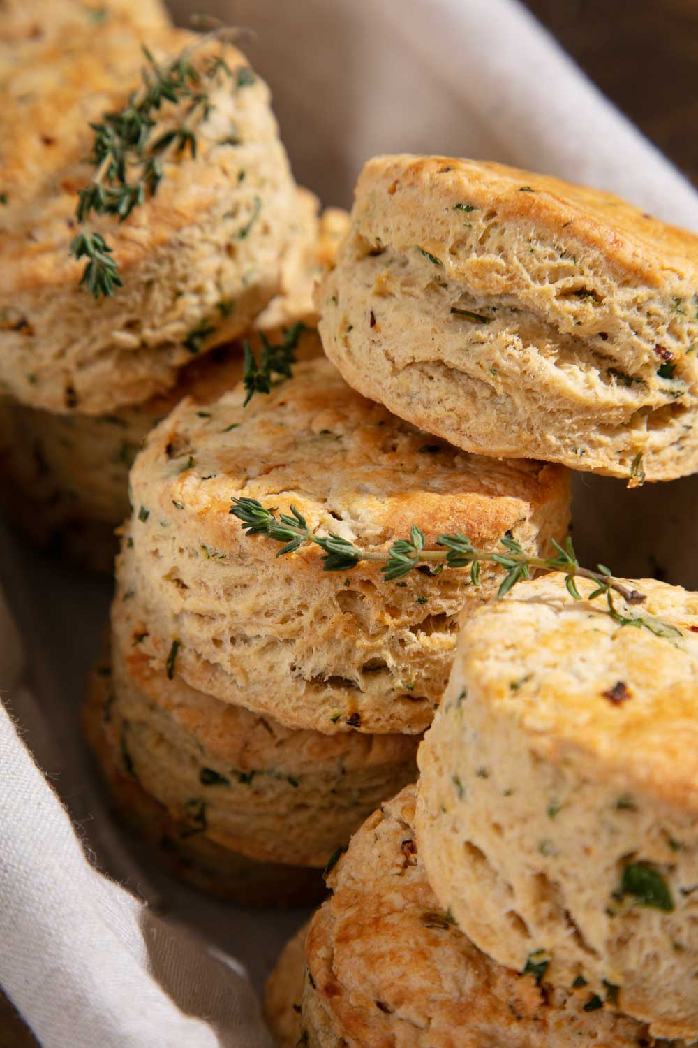 Vegan savoury scones with fresh thyme sprigs in a lined basket.