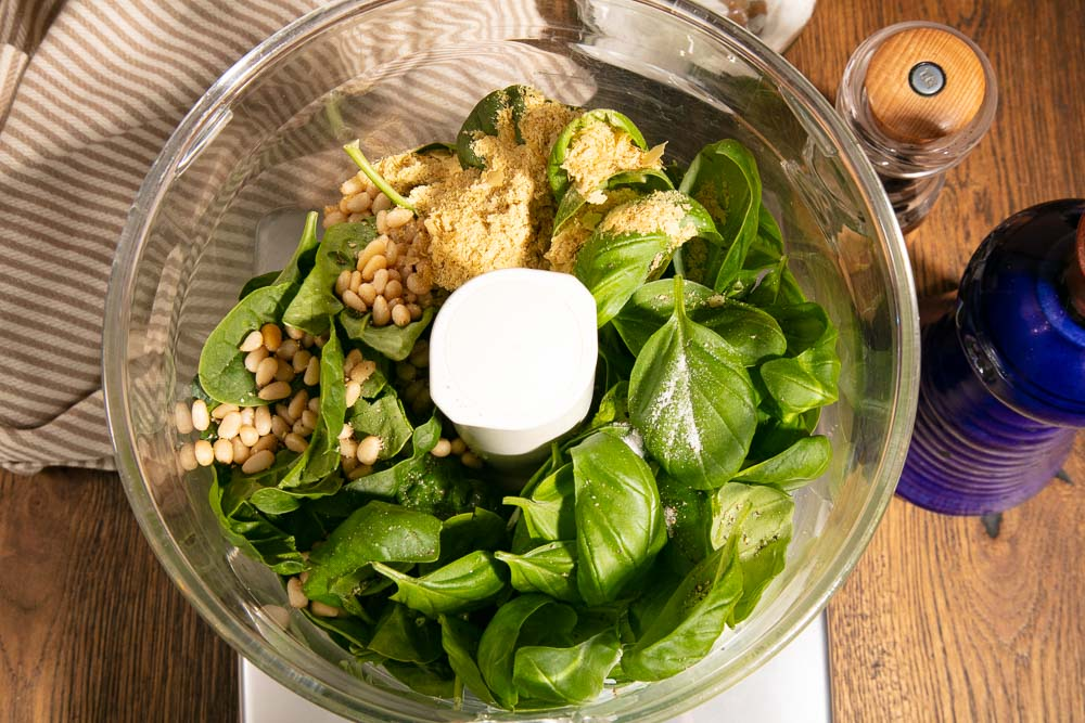 Ingredients for fresh pesto in the bowl of a food processor.