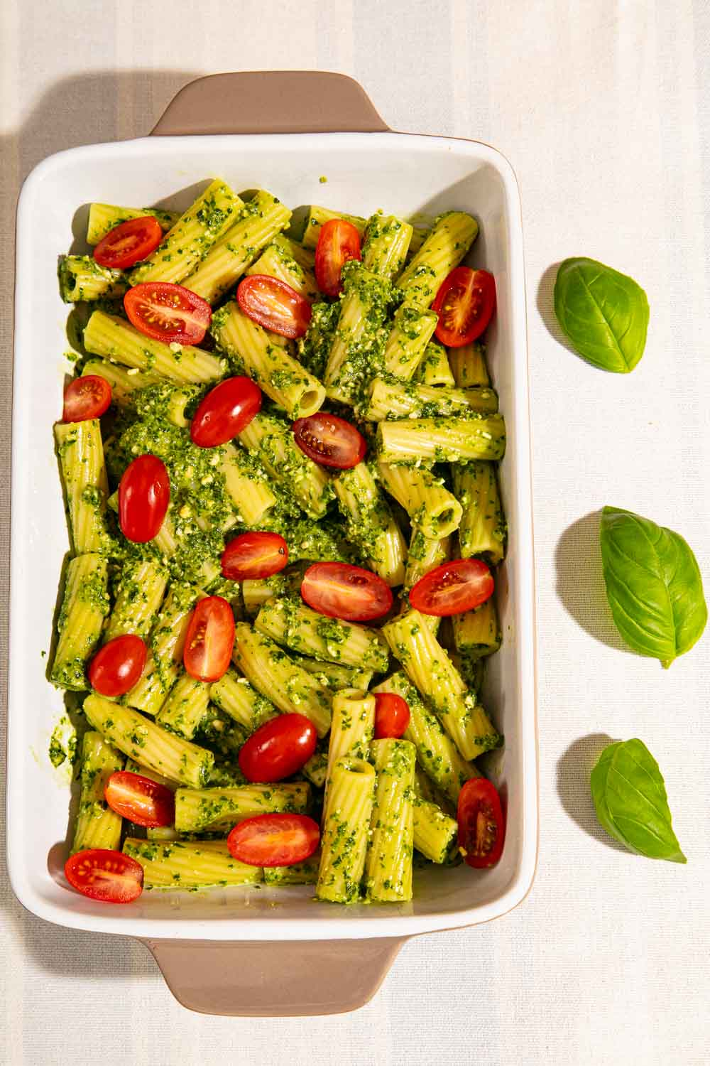 Pesto pasta Bake topped with tomatoes, ready for the oven.