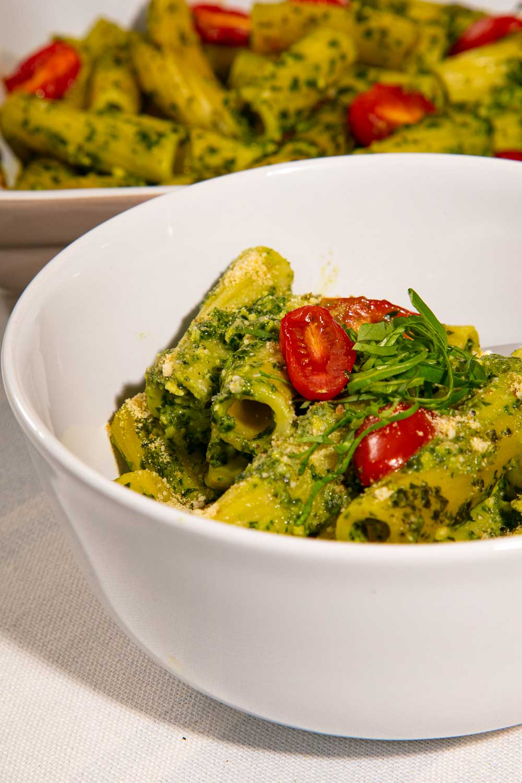 Vegan Pesto Pasta Bake topped with tomatoes and basil.
