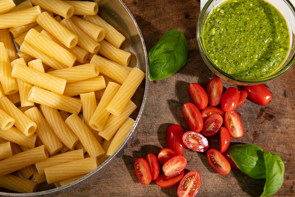 Cooked rigatoni pasta alongside a bowl of vegan pesto and some halved baby plum tomatoes.