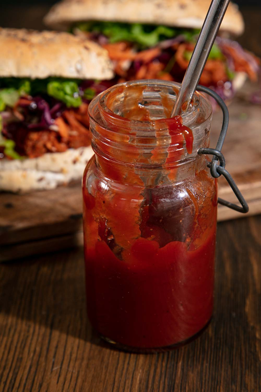 Half a jar of BBQ sauce in front of BBQd Jackfruit sliders.