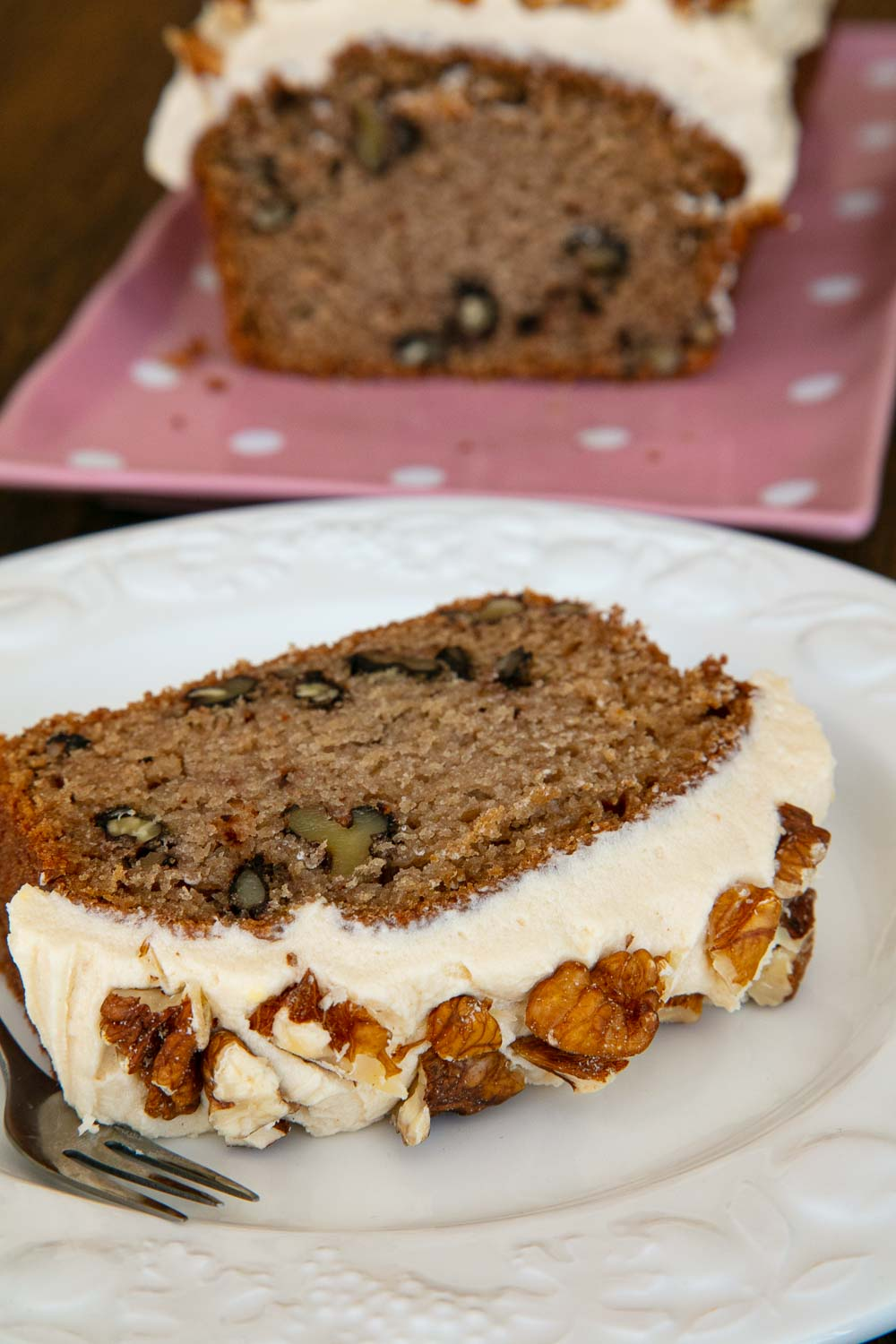 A slice of coffee and walnut cake topped with coffee buttercream and chopped walnuts.