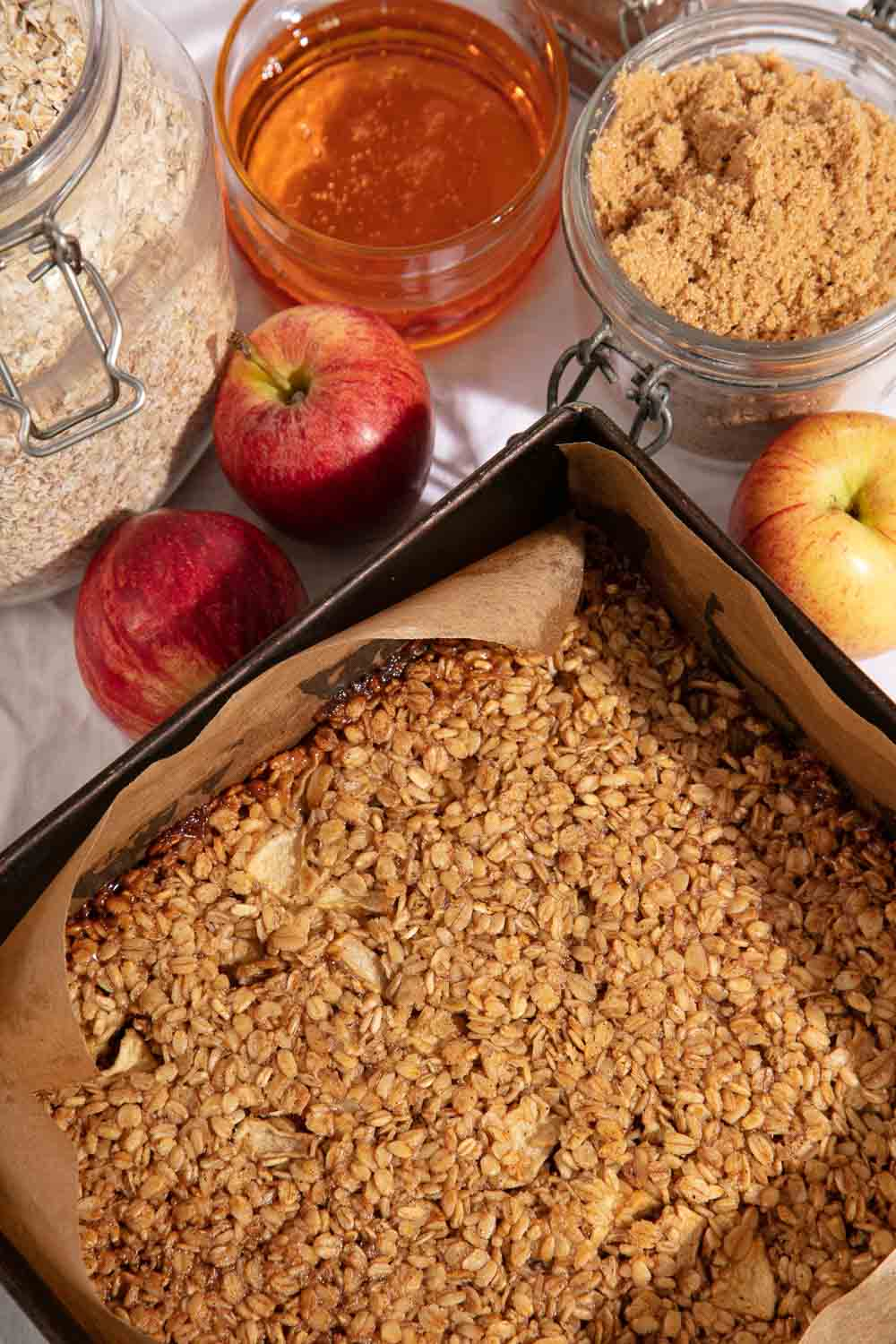 Cooked apple flapjack in its tin surrounded by the ingredients to make it.