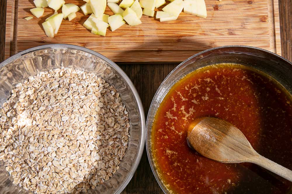 Oats in a bowl next to melted butter, syrup and sugar in a pan and chopped apples on a board.