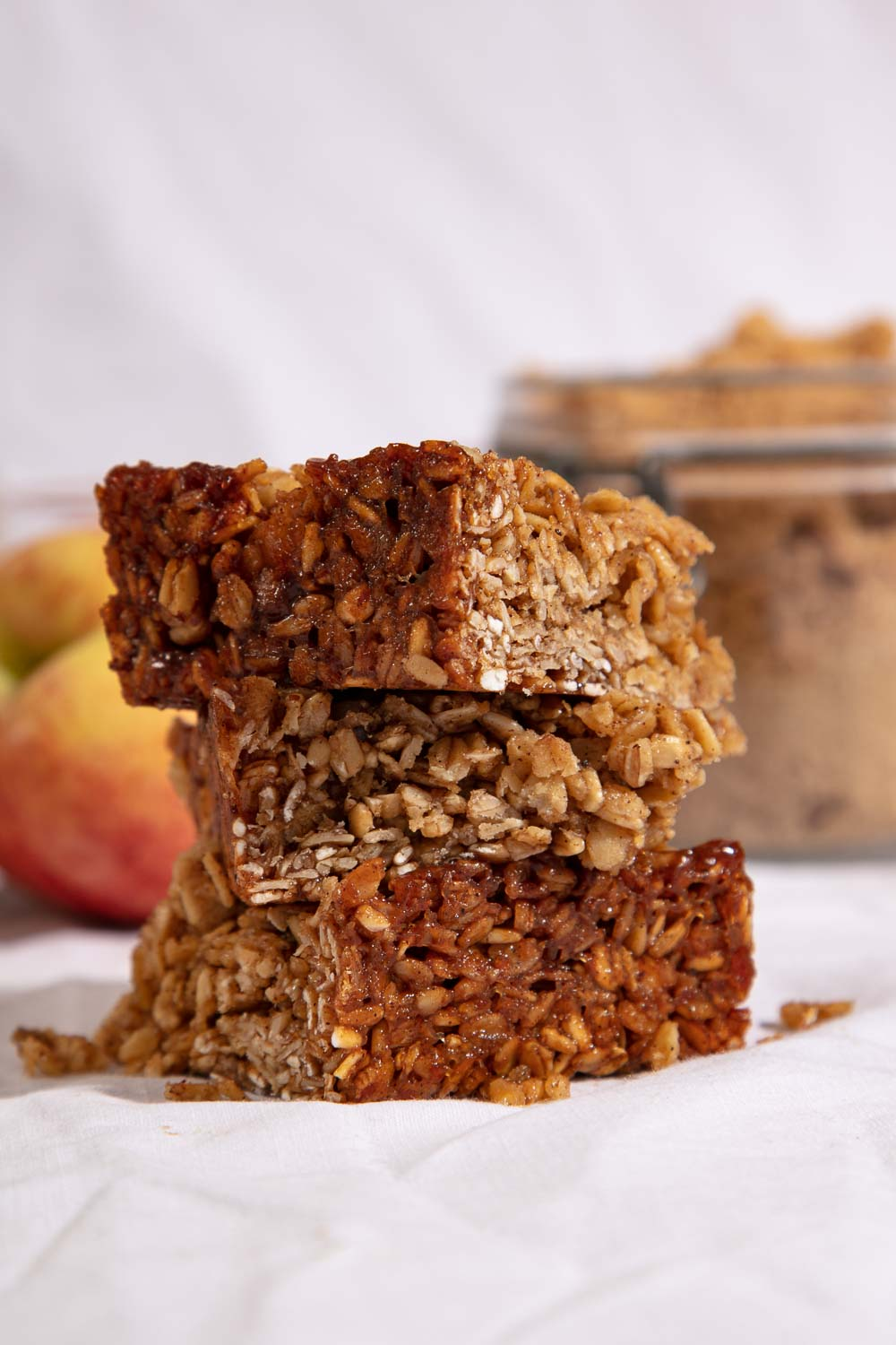 Stacked slices of apple and cinnamon flapjacks with the ingredients to make them in the background.