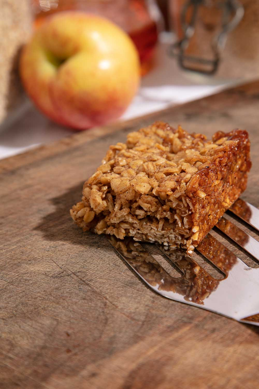 A slice of vegan apple and cinnamon flapjack on a wooden board.