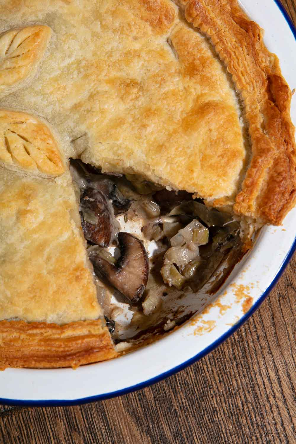 Leek and mushroom pie with a slice removed to show the filling.