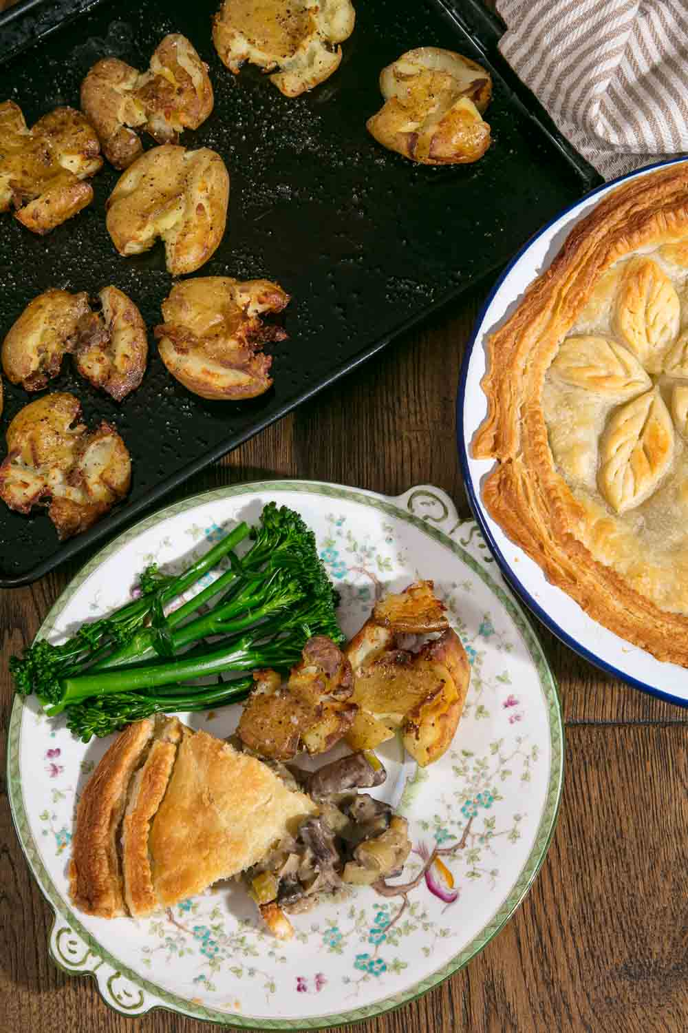 A slice of leek and mushroom pie on a plate with roasted potatoes and broccoli.